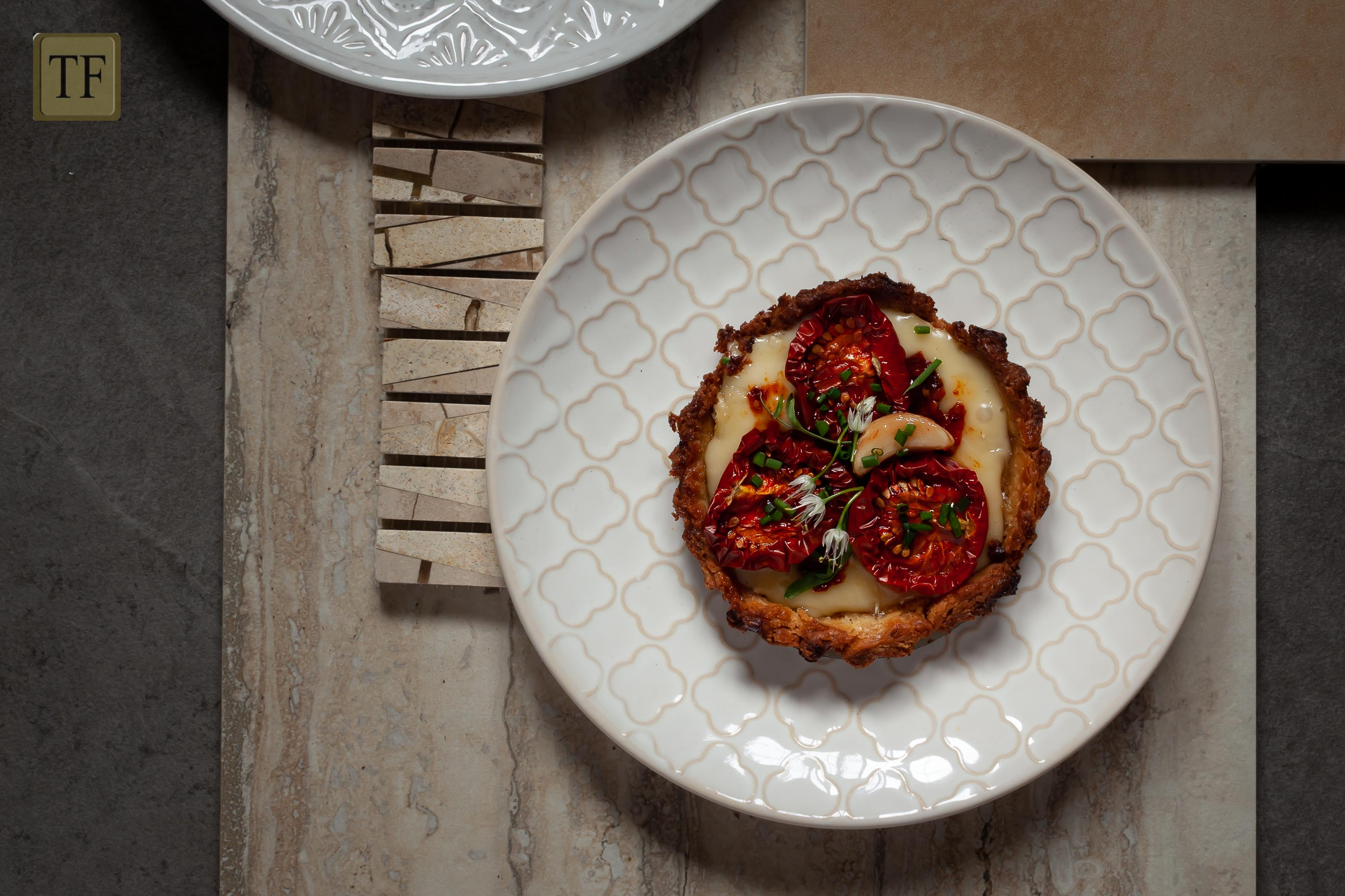 tomato tart made with garlic confit, dried tomatoes, tomato paste and brie